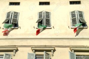 State flags of Italy on the windows of facade of house in city Reggio Emilia